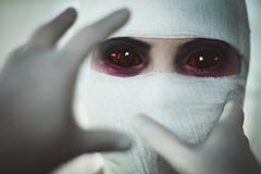Hands in surgical gloves are drawn to face Stock Photos