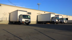 Trucks are lined up at a commercial warehouse and shipping facility. Stock Footage