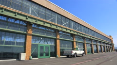 Wide shot of a large warehouse or factory with pickup truck in foreground. Stock Footage