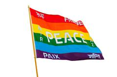 Rainbow varicolored pacifist flag with multilingual peace text isolated Stock Photos