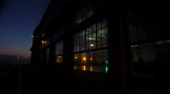Wide shot of a large warehouse or factory at dusk or sunset as a large cargo Stock Footage