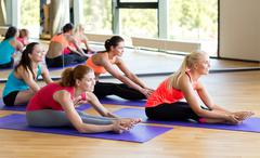 Group of smiling women stretching in gym Stock Photos