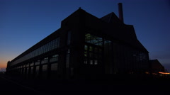 Wide shot of a large warehouse or factory at dusk or sunset. Stock Footage