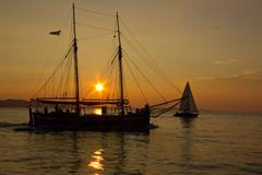 Sailing into the sunset with reflections on the sea surface Stock Photos