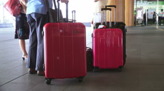 Red Rolling Suitcase And Travelers At Train Station Stock Footage