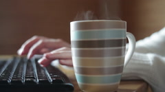 Striped mug of coffee on the table and keyboard - stock footage