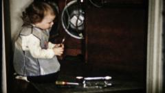 1742 - little girl plays electrician & repairs old radio-vintage film home movie Stock Footage