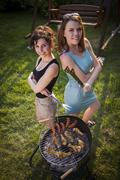 Two pretty girls making food on grill - stock photo
