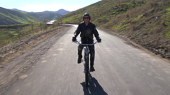 A man rides a motorized bicycle through the countryside on a two lane road. - stock footage