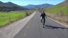 A man in leather jacket drives a motorized bicycle along a country road. Stock Footage