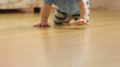 A little funny baby crawling on the floor, back view,slowmotion Stock Footage