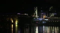Night scene of lake with paddleboats, bridge and citylights Stock Footage