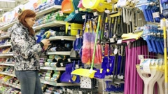 Woman choosing brush, broom, dustpan, rags, cleaning, cleaning, mop Stock Footage