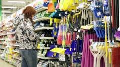 Woman choosing mop, broom, dustpan and cleaning Stock Footage