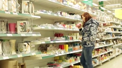 Woman in supermarket chose paraffin candles - stock footage