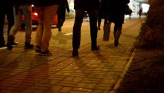 people walking on the street night - closeup legs - road with cars - stock footage