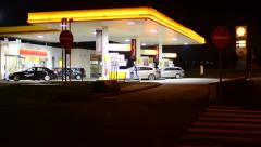 Gas station (oil pump) Shell in the city - with cars and people - night Stock Footage