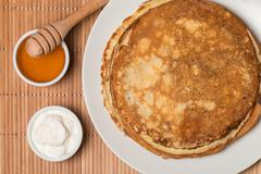 Pancakes with sour cream and honey Stock Photos