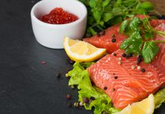 Fresh salmon and red caviar on black plate - stock photo