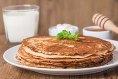 pancakes with sour cream, milk and honey - stock photo