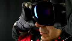 Skier/snowboarder putting his glasses on black background, close up Stock Footage