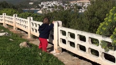 Baby learns to walk holding fence 2 Stock Footage