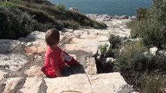 Baby on stone stairs above the sea Stock Footage