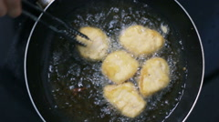 Stock Video Footage of Top view, Batter fried chicken nuggets are being cooked in a pan.