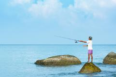 PHUKET Thai fisherman casts with his rod from a p - stock photo