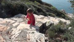 Baby on stone stairs studies the world Stock Footage
