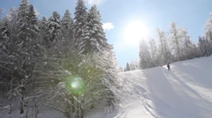 A winter scene, a ski slope at a mountain and two skiers passing by Arkistovideo