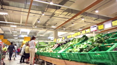 Buyers choose fresh vegetables and fruit in a supermarket Stock Footage