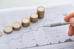 Hand With Pen Analyzing Line And Coin Graphs On Desk - stock photo