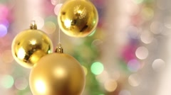 Three yellow Christmas balls hanging, with a colorful background - stock footage
