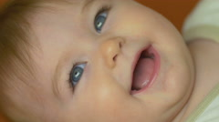 The baby lies on the bed look and smile. Close-up portrait view - stock footage