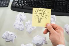 Businessman Holding Lit Bulb Drawn On Sticky Note Kuvituskuvat