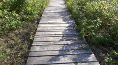 Walking on wooden path way in resort forest Stock Footage