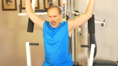 4K middle aged male doing arm pull down exercise Stock Footage