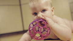 Сute little baby eating a toy and confusing slow motion - stock footage