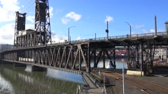 A passenger train crosses the steel bridge over the Willamette River in Portland Stock Footage