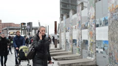 People passing by Berlin wall fragments at Potsdamer Platz - stock footage