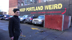 A man stands in front of a sign on a building urging visitors to keep Portland Stock Footage
