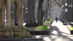An old man walks in the distance in a public park in Portland, Oregon. Stock Footage