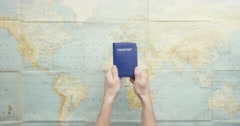 Top view hands holding american passport thumbs up gesture vintage world map Stock Footage