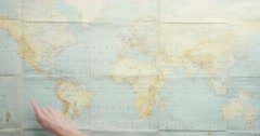Top view hands pointing at vintage world map  connecting global markets at desk Stock Footage