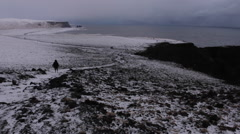 Person Walks By Snowy Cliffside Stock Footage
