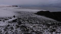 Person Walks By Snowy Cliffside Stock Footage