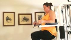 4k woman doing leg lift exercise on home gym machine Stock Footage