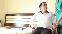 Young man in wheelchair transfering in bed Stock Footage