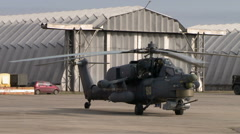 Military helicopter on background of hangars Stock Footage